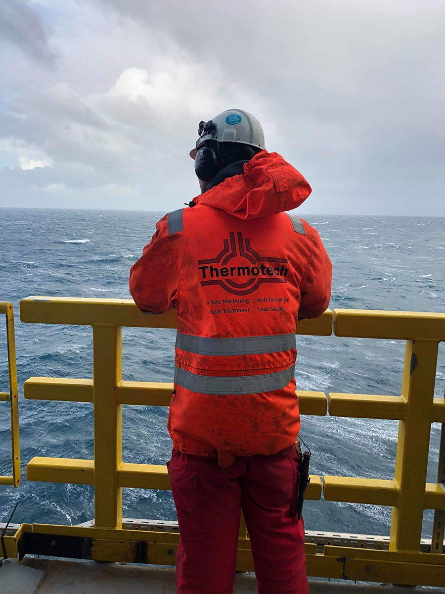 Thermotech operator standing on  a platform looking towards the sea